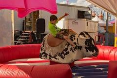 Child on Mechanical Bucking Bull Ride. Salem, VA – June 29th: A young boy riding a mechanical bucking bull ride at the 16th annual Salem Fair, Salem, VA, USA Stock Photos