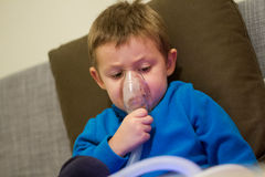 Child medical treatment. Child taking respiratory medical treatment with nebuliser Stock Image