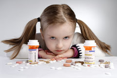 Child and medication. Sad little girl behind pile of medicine Royalty Free Stock Image
