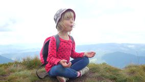 A child meditates in a lotus position on top of a mountain. stock video footage