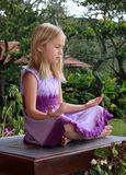 Child Meditating. A young girl quietly meditates in a tropical garden Royalty Free Stock Photos