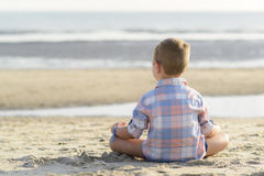 Child meditating on the beach Stock Photo