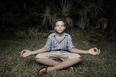 Child meditating on the grass Royalty Free Stock Images