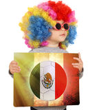 Child with Mexican soccer background. Little child with clown wig support Mexican team Royalty Free Stock Photo