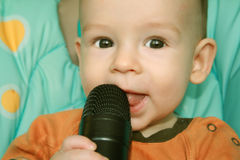 The child with a microphone. The child of 6 months sits with a microphone Royalty Free Stock Photo