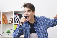 Child with the microphone singing. Children, teenager or preteen with the microphone singing at home royalty free stock photo