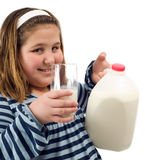 Child Milk. A young child holding a jug of milk along with a glass, isolated against a white background Stock Image