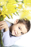 Child with mimosa in hand. Smiling child with mimosa in hand Royalty Free Stock Image