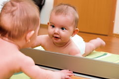 Child in the mirror. Child lying on the floor and watching yourself in the mirror Stock Images