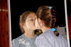 Child and mirror. A child is standing in front of mirror and kissing her own reflection Stock Images
