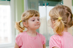 Child the mirror. Child watching itselt in the mirror Royalty Free Stock Photo