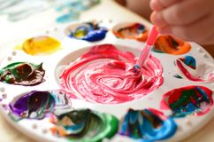 Child mixing paint on a palette of colorful paint Royalty Free Stock Photography