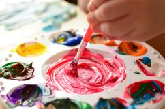 Child mixing paint on a palette of colorful paint Stock Photo