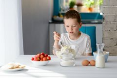 Child mixing white cottage cheese in a bowl. 7 year old boy mixing white cottage cheese in a bowl. Prepares mini cheesecakes with strawberries Stock Photography