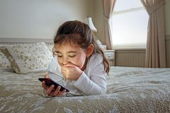 Child with mobile on bed Royalty Free Stock Images