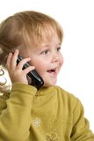 Child with mobile phone. Child in green talking by mobile phone Stock Images