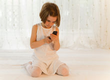 Child with mobile phone - cellphone with SMS Royalty Free Stock Photos