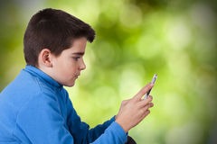 Child with mobile phone. On natural background blur Stock Images