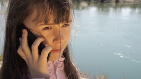 A child with a mobile phone by the river. The girl is talking on the phone in the fresh air. A spring sunny day. A girl with her hair in a pink jacket on the stock footage
