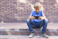 Child with mobile phone sitting outdoors. Boy looks at the screen, use application, plays. Sunny day. Brick wall royalty free stock image