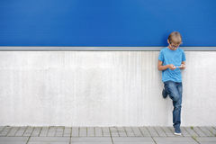 Child with mobile phone standing near blue and grey wall outside Stock Image