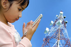 Child with mobile phone. Young girl using a cell phone tower as a backdrop Stock Photography