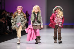 Child models wear fashions by Snowimage. MOSCOW - FEBRUARY 22: Three unidentified child models wear fashions by Snowimage and walk the catwalk in the Collection Stock Photos