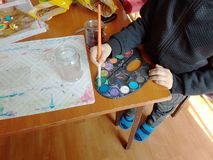 Child moistens the brush in a palette with multi-colored paints. Children`s creativity and painting science. Creative activity of. The growing generation stock photos