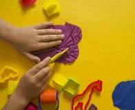 Child mold from colored plasticine.Children`s hand Stock Images