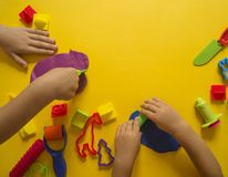 Child mold from colored plasticine.Children`s hand Stock Photos