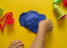 Child mold from colored plasticine.Children`s hand Stock Image