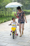 Child with mom. A happy child ride her bicycle  with Mom Royalty Free Stock Photo