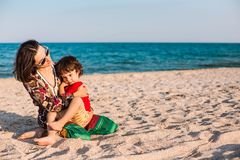 Child with mom on the beach. The boy is playing with his mother. The kid hugs Mom and smiles. A women is resting with her son at the seaside Royalty Free Stock Image