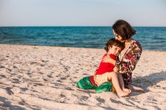 Child with mom on the beach. The boy is playing with his mother. The kid hugs Mom and smiles. A women is resting with her son at the seaside Stock Photos