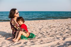 Child with mom on the beach. The boy is playing with his mother. The kid hugs Mom and smiles. A women is resting with her son at the seaside royalty free stock photos