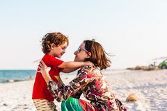 Child with mom on the beach. The boy is playing with his mother. The kid hugs Mom and smiles. A women is resting with her son at the seae Stock Images