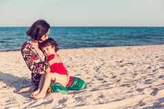 Child with mom on the beach. The boy is playing with his mother. The kid hugs Mom and smiles. A women is resting with her son at the seae Stock Photography