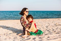 Child with mom on the beach. The boy is playing with his mother. The kid hugs Mom and smiles. A women is resting with her son at the seaside Stock Photography