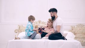 Child, mom and dad sit on bed, smiling and communicate. Young happy couple together in bedroom. Young family being stock video