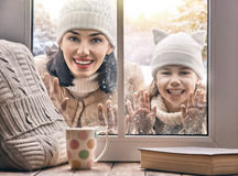 Child and mom looking in windows, standing outdoors Stock Image