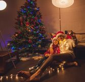 Smiling girl with mom near christmas tree at home Stock Photo