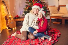 Smiling girl with mom near christmas tree at home Stock Photos