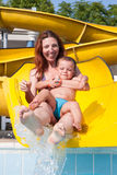 Child and mom playing with the slide in the pool Royalty Free Stock Image