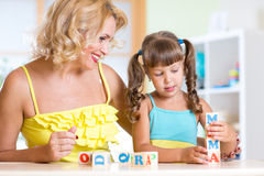 Child and mom playing wooden toys at home Stock Images