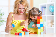 Child and mom playing wooden toys at home. Child and her mom playing wooden toys at home Royalty Free Stock Image