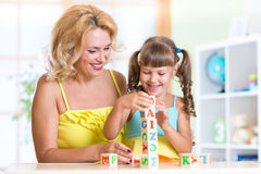 Child and mom playing wooden toys at home Royalty Free Stock Image