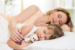 Child with mom preparing for napping on bed Royalty Free Stock Images