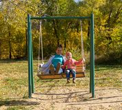 Child with mom ride on a swing in autumn stock photos