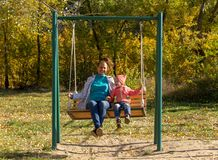 Child with mom ride on a swing in autumn royalty free stock image