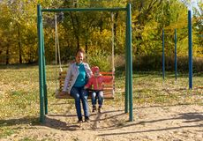Child with mom ride on a swing in autumn royalty free stock photography